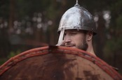 Man in helmet looks uncertain, holds up shield. Photo by Shutterstock