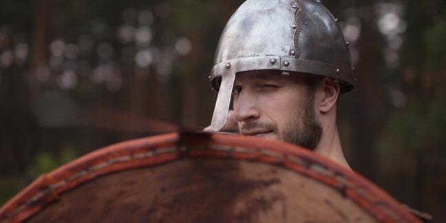 Man in helmet looks uncertain, holds up shield. Photo by Shutterstock