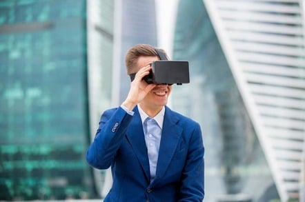 Smiling man wears VR headset against backdrop of city. Photo by Shutterstock