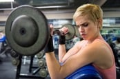 Woman at gym lifts weights with arms. Photo by Shutterstock
