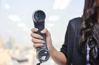 Woman holds up PBX phone in office. Pic by Shutterstock