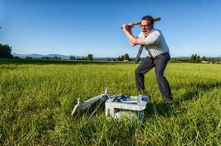 Man in tie smashes printer with baseball bat in a field.