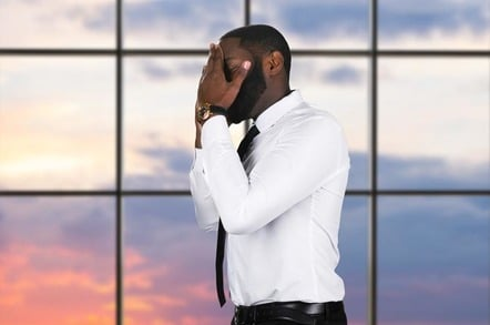 Man in suit performs double facepalm, presumably after witnessing incident of great stupidity. Photo by shutterstock