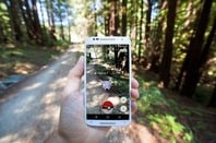 "The hit augmented reality smartphone app ""Pokemon GO"" shows a Pokemon encounter overlain on a real world trail in the forest in Santa Cruz, California. Photo by Matthew Corley for Shutterstock. EDITORIAL USE ONLY!."