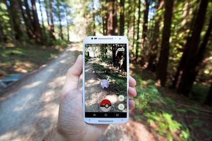 """The hit augmented reality smartphone app """"Pokemon GO"""" shows a Pokemon encounter overlain on a real world trail in the forest in Santa Cruz, California. Photo by Matthew Corley for Shutterstock. EDITORIAL USE ONLY!."""