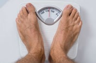 Man weighs himself on imperial scale. photo by shutterstock