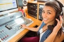 Young woman in headphones sits at mixing desk in radio/podcast studio. Photo by Shutterstock