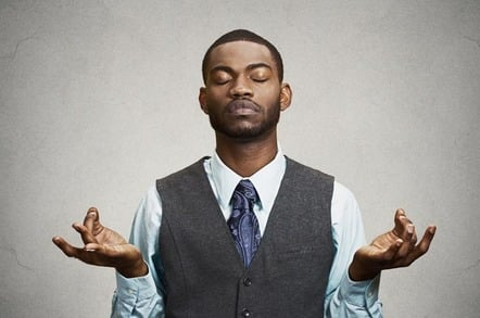 Suit-and-tie-wearing man tries to meditate, take deep breaths in faux yoga pose. Photo by Shutterstock