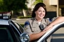 A US police officer smiles while standing in front of her patrol car. Photo by Shutterstock