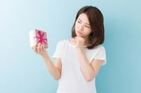 Thanks, I suppose. Woman contemplates unwanted gift. Photo by Shutterstock