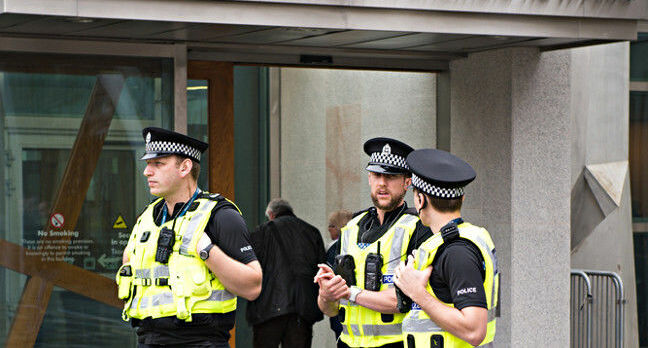 Police Scotland employees stand outside the Scottish Parliament. Pic: Shutterstock