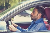 Terrified man clutches steering wheel of car. Photo by shutterstock