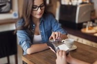 Woman uses card reader at coffeee shop. Photo by Shutterstock