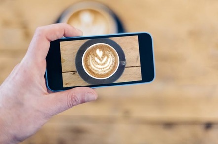 mBILE TAKING PICTURE OF A CUP OF COFFEE. Photo by SHutterstock