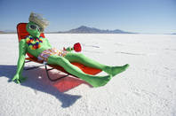 Green space alien with sombrero and drink on a sun lounger