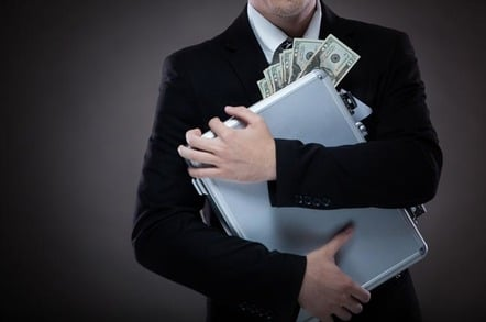 man in suit clutches briefcase full of cash. Photo by Shutterstock