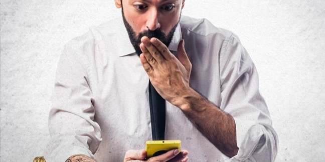Man looks at his mobile - mildly surprised or shocked about something. Photo by shutterstock
