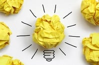 "Idea conceptual illustration: Loads of crumpled up balls of paper and one ""shining lightbulb one"" (the good idea). Photo by Shutterstock"