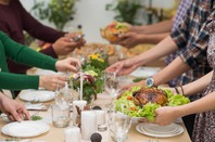 People sit down to a meal at a table. Photo by Shutterstock