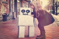 Little girl embraces robot. Photo by Shutterstock