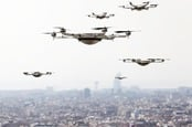 Drones hover above a smart city. Photo by shutterstock