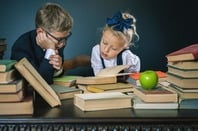 Schoolkids in uniform studying with books/apple. Photo by shutterstock