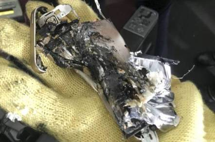 The crushed personal electronic device (PED) wedged tightly in the seat mechanism found on QF 7