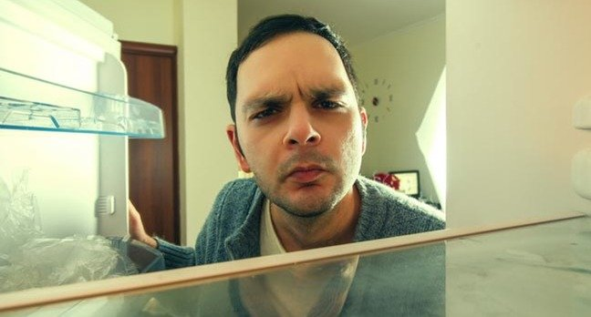 Man peers into fridge with odd look on his face. Photo by shutterstock