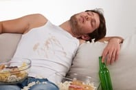 Sleeping man on couch with a beer , popcorn and a food-stained vest. Photo by Shutterstock