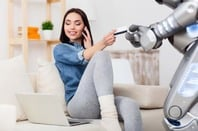 Woman hands credit card to robot while chatting on her mobile phone. Photo by Shutterstock