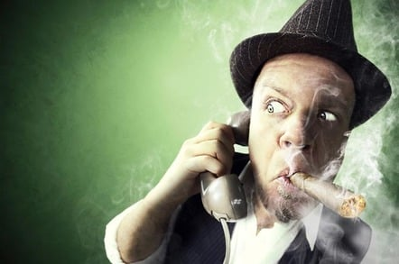 PRIVATE investigator on the phone, smoking a cigar, looks around suspiciously. Photo by Shutterstock