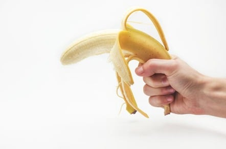 Man holds banana like a gun. Photo by Shutterstock