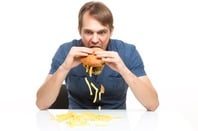 Man sloppily eats a hamburger... chips and pickle fall out. Photo by Shutterstock