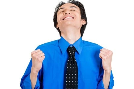 Man in blue shirt and tie raises face to the sky in bliss during double fist-pump. Photo by Shutterstock