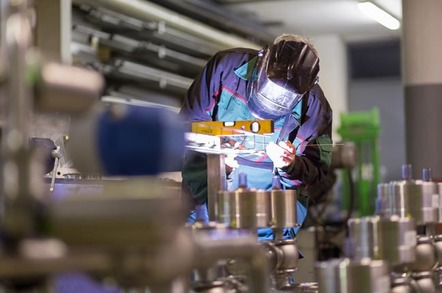Worker welds at manufacturing plant. Phto by Shutterstock
