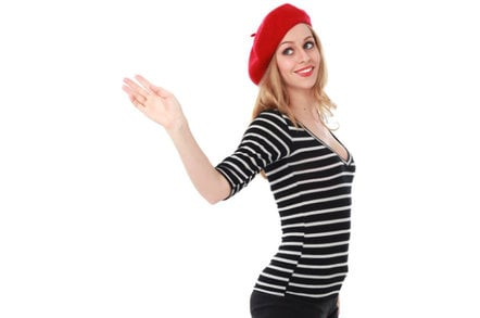 woman in beret representing France waves goodbye, perhaps to Brexiting British? photo by shutterstock