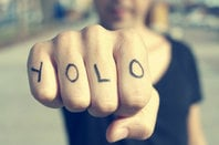 Man with YOLO tattooed on his knuckles prepares to punch the viewer (of the pic). Photo by Shutterstock