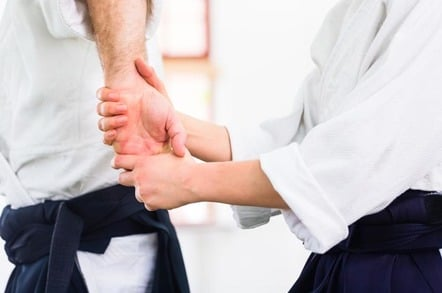 person twists another's arm. Photo by shutterstock