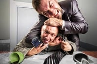 Two angry businessmen fighting over agreement signing. Coffee is spilled. .Photo by Shutterstock