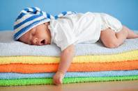 Yawning sleeping baby on colourful stack of towels