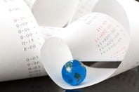 roll of figures on adding machine ledger with a world map globe nestling in the folds...Photo by Shutterstock