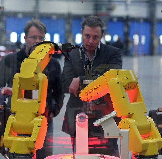 The yellow robot arms dance through an assembly demo for Elon Musk and the rest of the tour group that visited the reopening of the former NUMMI plant, now Tesla Motors. photo by Steve Jurvetson licensed under CC 2.0 must attribute