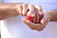 Bowler holds cricket ball. Photo by SHutterstock