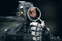 Robot looks into magnifying glass, human eye displayed. Photo by Shutterstock
