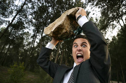Man heaves giant rock above his head in the middle of the woods. Photo by Shutterstock