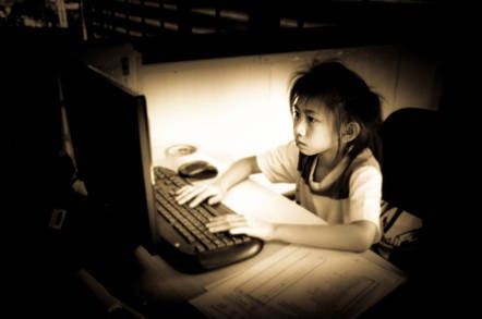 child looks downcast on a computer. Photo by Shutterstock