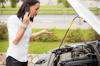 Woman chats on phone next to open hood after car breaks down. Photo by SHutterstock
