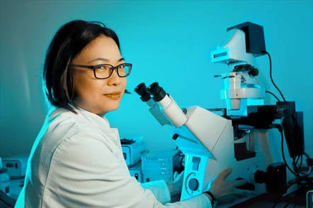 WHite lab coated scientist looks sceptical in front of microscope. Photo by Shutterstock
