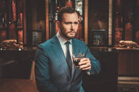 Well-dressed man drinks whisky in expensive flat. Photo by Shutterstock