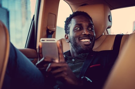 Passenger in back of cab using smartphone app/cab app. Photo by Shutterstock